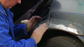 Mężczyzna czyści ślada rdza od samochodowego ciała z szmerglowym papierem Czasu up?yw zdjęcie wideo