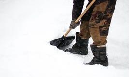 Mężczyzna czyści śnieg z łopatą Okurzanie śnieg z bliska obraz stock