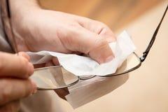 Mężczyzna czyści oczu szkła z białym płótnem, cleanliless obiektyw obraz stock