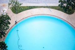 Mężczyzna czyści pływackiego basenu z Próżniowym cleaner obraz stock