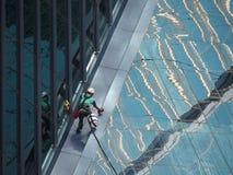 Mężczyzna czyści szklanego budynek fotografia royalty free