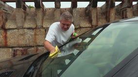 Mężczyzna czysty samochodowy okno przy plenerowym zbiory wideo