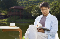 Mężczyzna czytać plenerowy w ranku Zdjęcia Royalty Free