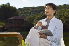 Mężczyzna czytać plenerowy z kawą w ręce Obraz Stock