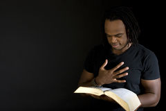 Mężczyzna czyta biblię odizolowywającą na czerni Zdjęcie Royalty Free