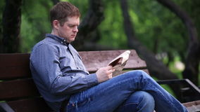 Man reads newspaper on bench in the park 2 Stock Footage