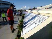 Mężczyzna czyta imiona w zabytku w wspominaniu tamto które znikali w burza przypływie przynoszącym tajfunem Yolanda obraz royalty free