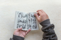 Mężczyzna czyta komiksowi zwanego starego mistrza Q Obraz Royalty Free