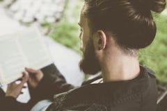 Mężczyzna czyta książkę outdoors obraz stock