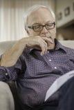 Mężczyzna czyta książkę w domu Zdjęcia Stock