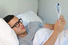 Mężczyzna czyta magazyn w łóżku obrazy royalty free