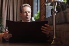 Mężczyzna czyta menu. Ufnego dojrzałego biznesmena czytelniczy menu przy t Fotografia Royalty Free