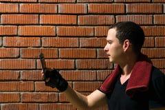 Mężczyzna czyta treningu plan na smartphone na czerwonym ściana z cegieł tle w gym obrazy stock