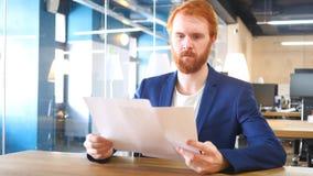 Mężczyzna czytania papiery w biurze Fotografia Royalty Free