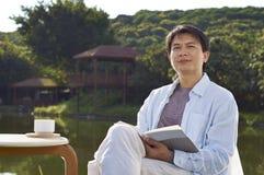 Mężczyzna czytanie przy nadbrzeżnym w ranku Obraz Stock