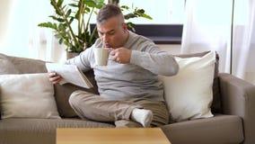 Mężczyzna czytelnicza gazeta i pić w domu kawa zdjęcie wideo