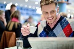Mężczyzna czytelnicza gazeta przy plenerową kawiarnią Obraz Royalty Free