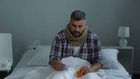 Mężczyzna czytelnicza instrukcja dla środka przeciwwirusowego narkotyzuje kasłać siedzieć w łóżku, złapany zimno zdjęcie wideo