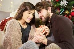 Mężczyzna daje boże narodzenie teraźniejszości dziewczyna w domu Fotografia Stock
