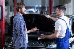 Mężczyzna daje motorowemu mechanika kluczowi Fotografia Stock