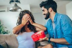 Mężczyzna daje niespodzianka prezentowi kobieta fotografia royalty free