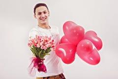 mężczyzna daje tulipany i sercowatych balonom zdjęcie royalty free