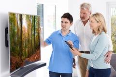 Mężczyzna Demonstruje Nową telewizję Dorośleć pary W Domu Zdjęcie Stock