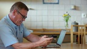 Mężczyzna dojrzały wiek pracuje z laptopu, telefonu i banka kartami, Ustanawia rozkaz w twój swój kontach, wynagrodzenie rachunki zbiory wideo