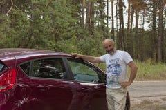Mężczyzna dojrzały wiek w lesie drogą stawia jego rękę na ciele samochód zdjęcia stock