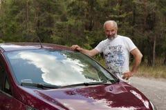Mężczyzna dojrzały wiek w lesie drogą stawia jego rękę na ciele samochód zdjęcie royalty free