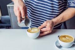 Mężczyzna dolewania mleko w kawę Fotografia Royalty Free