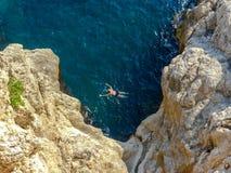 Mężczyzna dopłynięcie w otwartej wodzie blisko falez na zewnątrz starych grodzkich ścian Dubrovnik zdjęcia stock