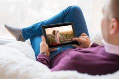 Mężczyzna dopatrywania film na pastylce w domu obrazy royalty free