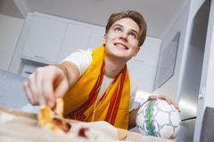 Mężczyzna dopatrywania sport na tv łasowania samotnej pizzy w domu obrazy stock