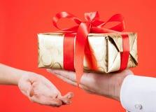 Mężczyzna dosięga out prezent młoda kobieta Zdjęcie Royalty Free