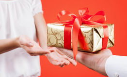 Mężczyzna dosięga out prezent młoda kobieta Fotografia Stock