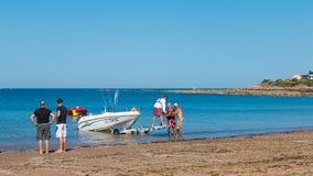 Mężczyzna dostaje łodzie z wody na plaży Zdjęcia Royalty Free