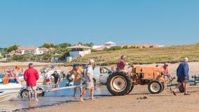 Mężczyzna dostaje łodzie z wody z ciągnikami na plaży Zdjęcia Royalty Free