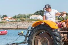 Mężczyzna dostaje łodzie z wody z ciągnikami na plaży Zdjęcia Stock