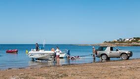 Mężczyzna dostaje łodzie z wody z samochodem na plaży Obrazy Stock