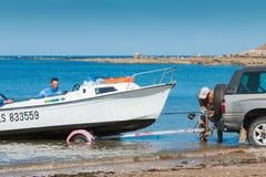 Mężczyzna dostaje łodzie z wody z samochodem na plaży Obraz Stock