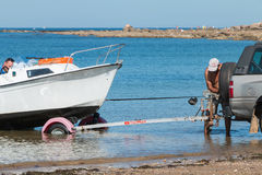 Mężczyzna dostaje łodzie z wody z samochodem na plaży Obraz Royalty Free