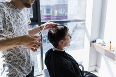 Mężczyzna dostaje ostrzyżenie przy fryzjera męskiego sklepem Fryzjera tytułowania włosy klient przy salonem zdjęcia royalty free