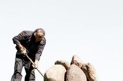 Mężczyzna dosunięcia kamienie z pitchfork na jaskrawym nieba tle Zdjęcia Stock