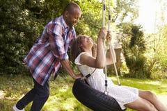 Mężczyzna dosunięcia kobieta Na opony huśtawce W ogródzie Fotografia Royalty Free