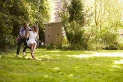 Mężczyzna dosunięcia kobieta Na opony huśtawce W ogródzie Zdjęcie Royalty Free
