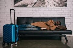 Mężczyzna drzemanie na czarnej kanapie zdjęcie stock