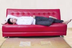 Mężczyzna drzemanie na czerwonej kanapie Zdjęcie Stock