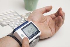 Mężczyzna egzamininuje ciśnienie krwi cyfrowa krwi wysokość odizolowane monitor preasure ciśnienie makro Obraz Stock