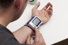 Mężczyzna egzamininuje ciśnienie krwi cyfrowa krwi wysokość odizolowane monitor preasure ciśnienie makro Obraz Royalty Free